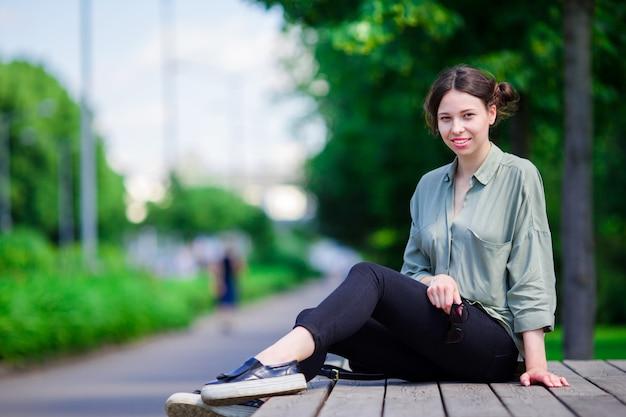 公園で幸せな若い都市女性。白人観光客は、暖かい夏の日の屋外をお楽しみください。