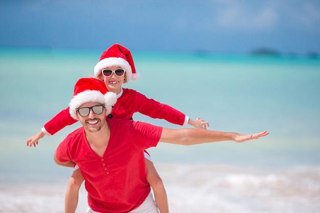 Маленькая девочка и счастливый отец в шляпу санта во время пляжных рождественских каникул