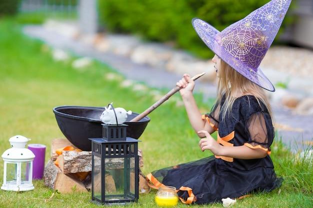 幸せな小さな魔女は屋外でハロウィーンを楽しんでいます。トリック・オア・トリート。