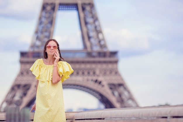 パリのエッフェル塔で電話で話している若い女性