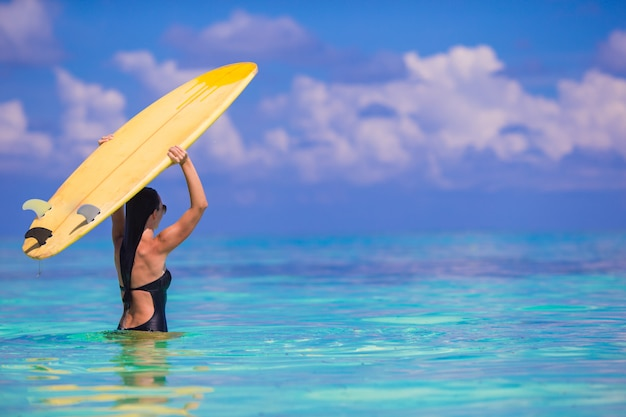 Счастливая стройная женщина для серфинга на белом пляже с желтой доской для серфинга