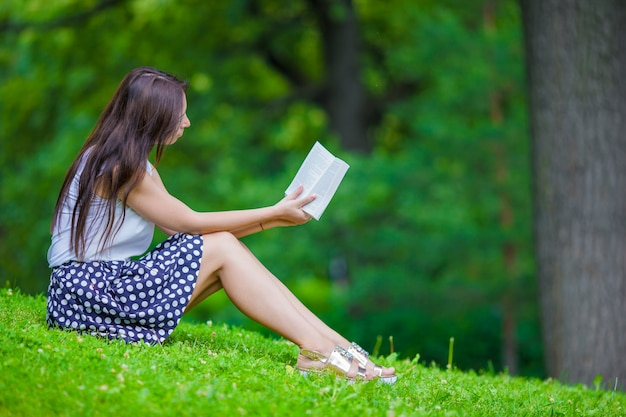 公園の外の本を読んでいる若い女の子
