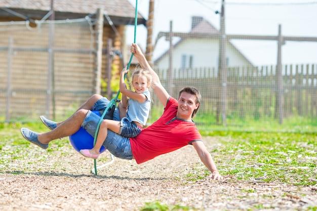 Счастливая семья весело на качелях на открытом воздухе