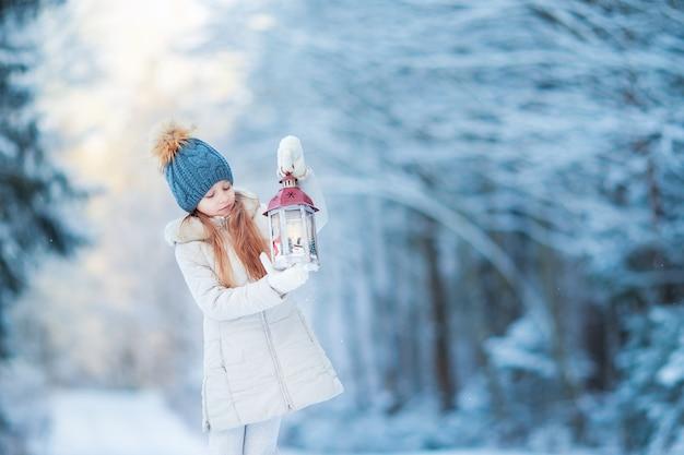 冬の森屋外でクリスマスに懐中電灯を持つ愛らしい少女