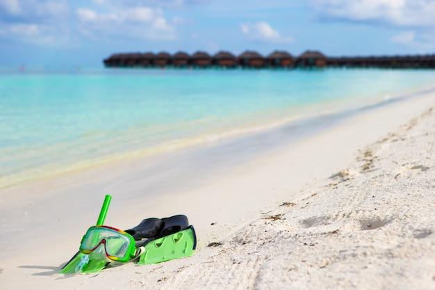 白い砂浜でシュノーケリング用のマスク、シュノーケル、フィン