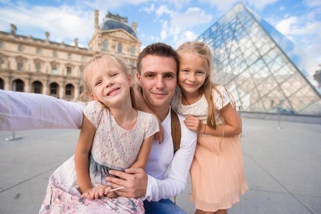 Счастливая семья с двумя детьми делает селфи в париже