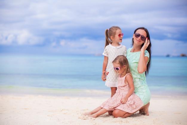 熱帯の白いビーチで愛らしい小さな女の子や若い母親
