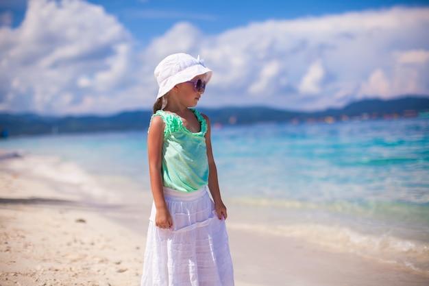 白い砂浜で熱帯の休暇に愛らしい笑顔の女の子