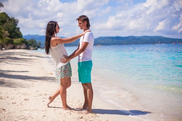 休暇を楽しんでいる若いカップルと熱帯のビーチで楽しい時を過す