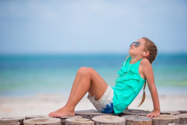 Маленькая прелестная девушка слушая к музыке на наушниках на пляже