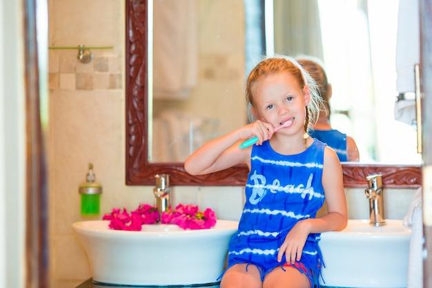 歯科衛生。彼女の歯を磨く愛らしい小さな笑顔の女の子