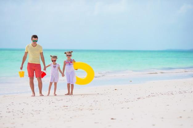 ビーチで夏休みを楽しんでいる若い家族