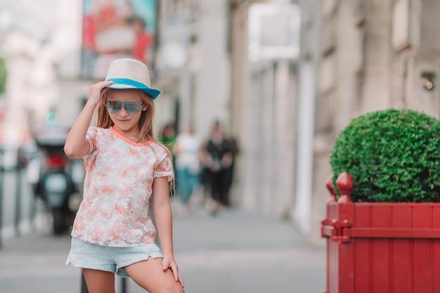 愛らしいファッションヨーロッパの都市で屋外の小さな女の子