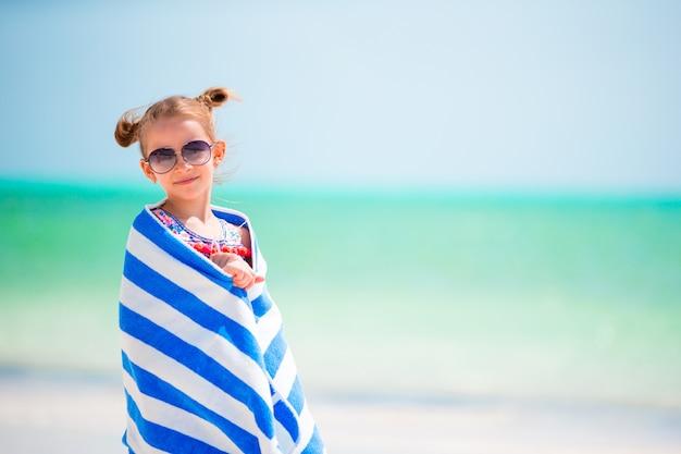 熱帯のビーチで泳いだ後タオルに包まれたかわいい女の子