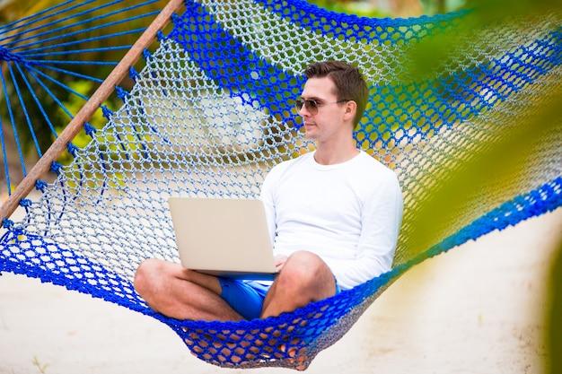 熱帯の休暇のハンモックでラップトップを持つ若者