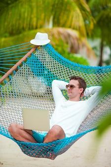 Молодой человек отдохнуть в гамаке на пляже тропический отдых