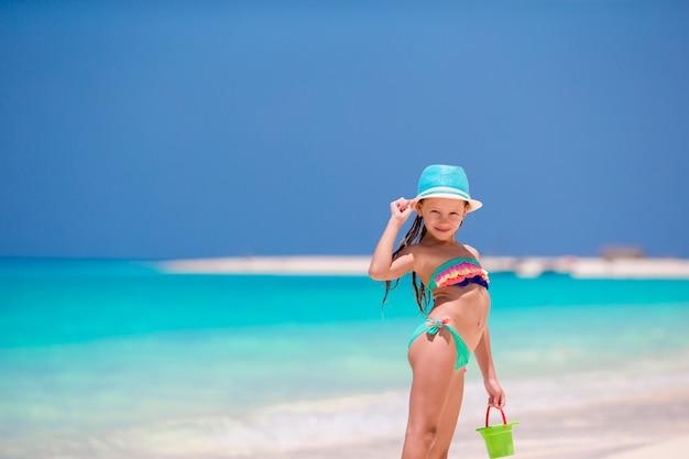 Очаровательны маленькая девочка в шляпе на пляже во время летних каникул