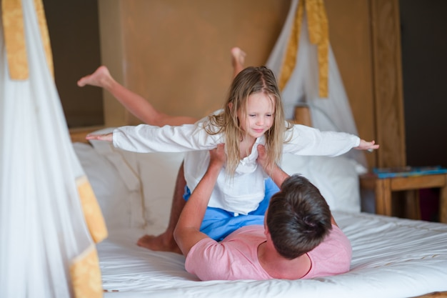 Отец играет с дочерью, играющей дома
