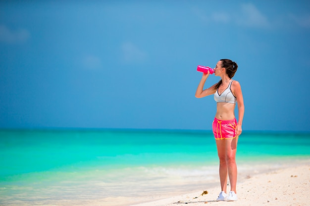 白いビーチにフィットする若い女性飲料水