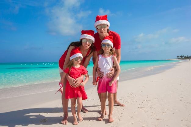 Счастливая семья из четырех человек на пляже в красных шляпах санта