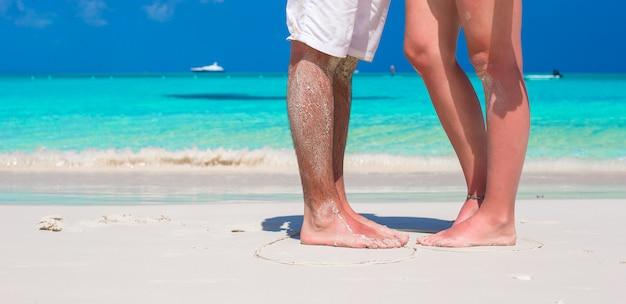 白い砂の上の男性と女性の足を閉じる