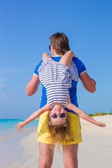 幸せなパパは完璧なビーチで彼の小さなかわいい女の子と楽しい時を過す