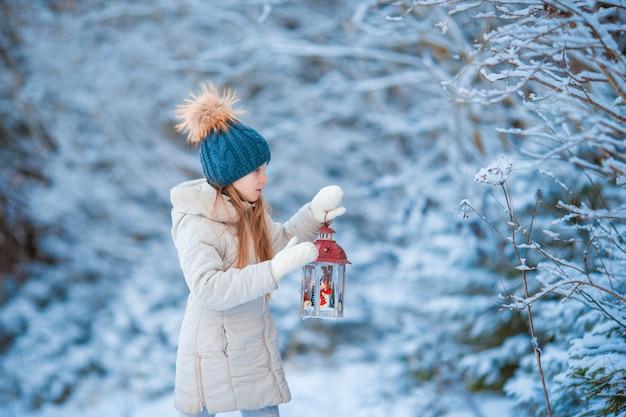 懐中電灯を持ってクリスマスの日に屋外で暖かいコートを着てのかわいい女の子