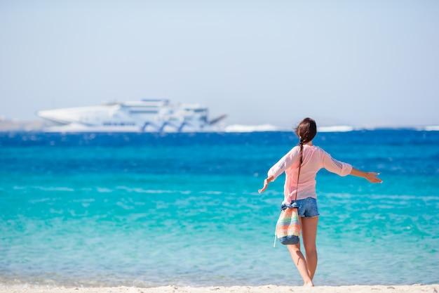 Молодая девушка на пляже фоне большой круизный лайнер. женщина наслаждается своим выходным на одном из красивейших пляжей греции, европы.