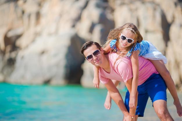 Счастливый отец и его очаровательная маленькая дочь на тропическом пляже, с удовольствием