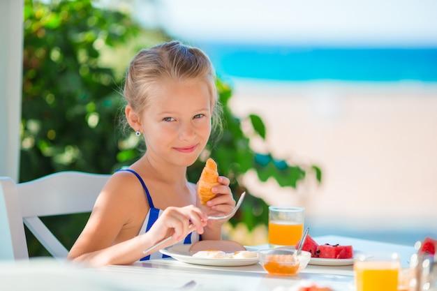 ランチタイム。海の景色と屋外カフェで朝食を持っている少女