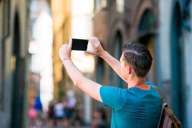 ローマの狭いイタリアの通りを歩いて手でスマートフォンを持つ白人観光客。ヨーロッパの都市を探索する休暇の都市少年