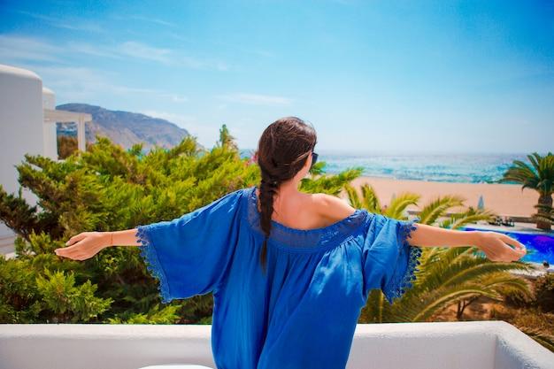若い幸せな女は彼女のバルコニーから海の景色をお楽しみください