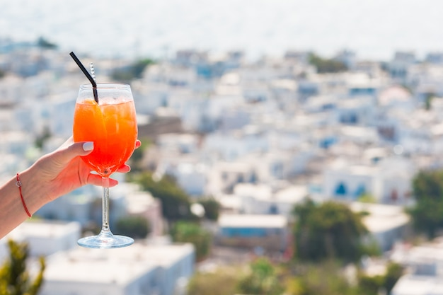 ギリシャの美しい古いミコノスのスプリッツアペロールアルコール飲料の背景を持つガラスを持っている女性の手