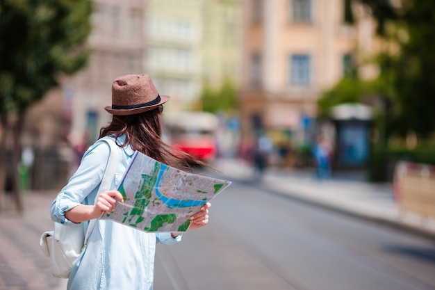 Молодая женщина, глядя на туристическую карту города. счастливая девушка наслаждается каникулами праздника в европе.