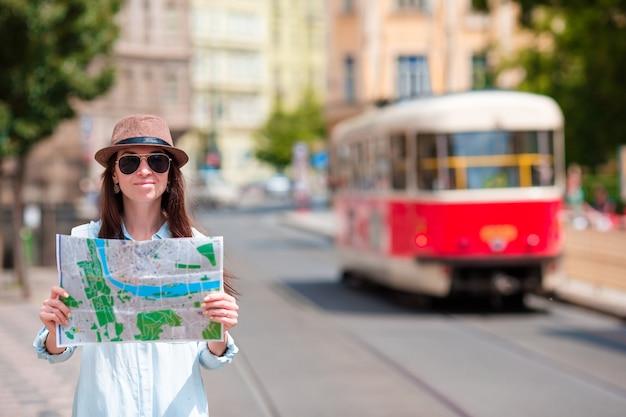 屋外観光名所を検索する市内地図と若い観光客の女の子。ヨーロッパでの休暇中に外の地図で白人女性を旅行します。