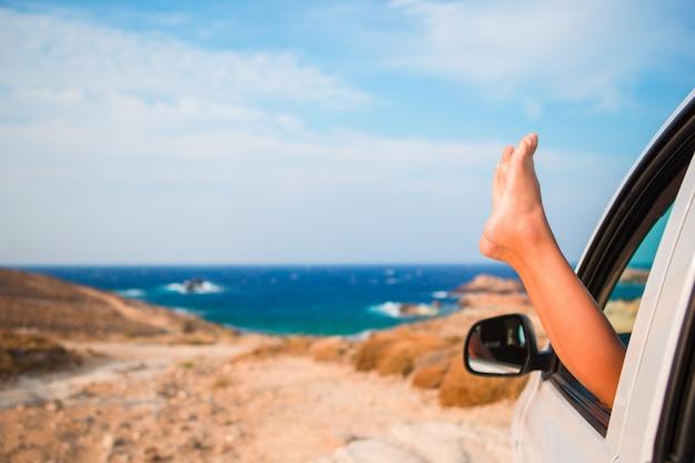 Закройте вверх ног маленькой девочки показывая от моря предпосылки окна автомобиля