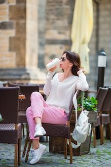 ヨーロッパでコーヒーを飲んで幸せな若い都市女性。白人観光客は、空の街で彼女のヨーロッパの休暇を楽しむ