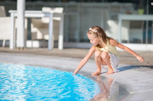 Маленькая девочка с удовольствием с всплеск возле бассейна