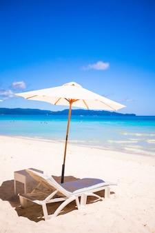 Два стула и зонтик на потрясающем тропическом пляже