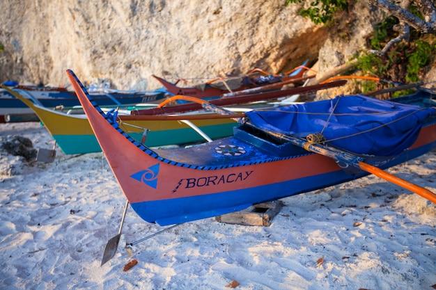 Филиппинская лодка на белом песчаном пляже в боракай, филиппины