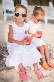 Очаровательная маленькая девочка, пить свежий арбуз на пляже