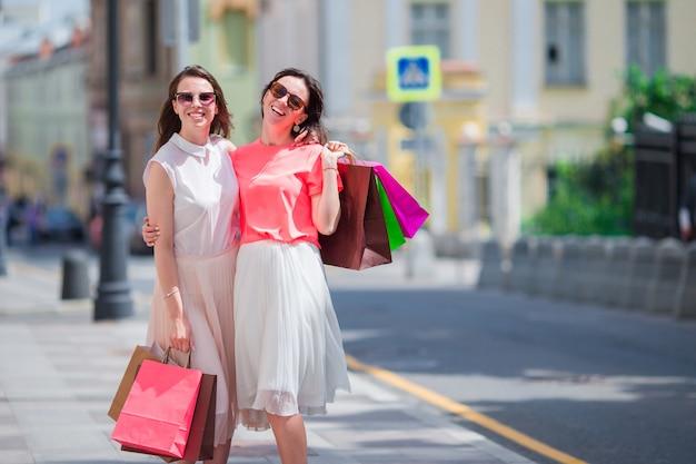 街の通りに沿って歩いて買い物袋を持つ若い女の子をファッションします。