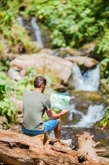 ジャングルの滝の景色を楽しみながら男