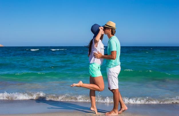 熱帯の休暇中にビーチで歩く美しい若いカップル