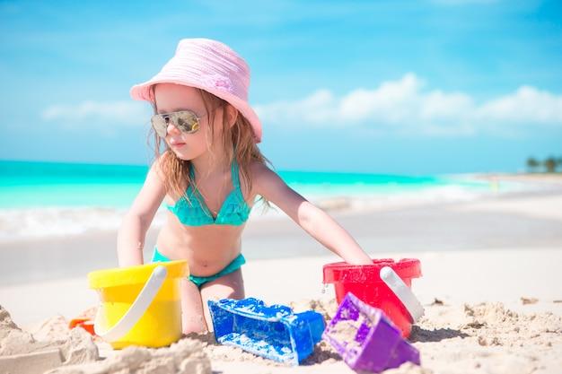 Милая маленькая девочка, играя с игрушками, пляж на берегу моря