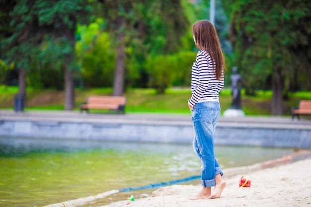 暖かい日に湖の近くを歩く若い幸せな女