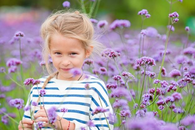 Маленькая прелестная девушка пахнущие красочные цветы на открытом воздухе