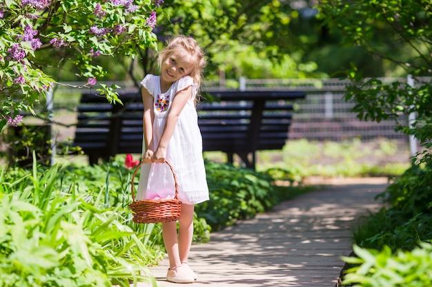 Маленькая прелестная девушка с цветами в саду тюльпанов