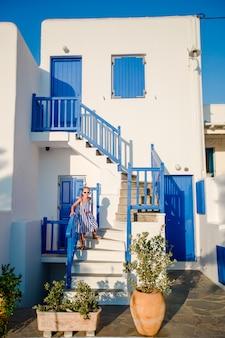 青いバルコニー、階段、花のある典型的な家。伝統的なギリシャの家の階段の上の少女。キクラデス様式の美しい建築建物の外観。
