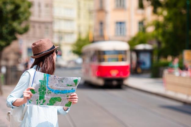 Красивая женщина, глядя на туристический план в риме, италия. счастливая девушка наслаждается итальянским праздником каникул в европе.